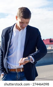 young man looking at his watch on the street