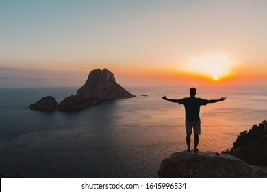 A young man looking into a colorful sunset in ibiza and spreading his arms