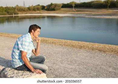 Young man looking at a lake