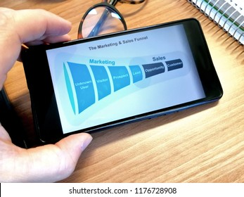 Young man looking at a Marketing sales funnel on the display of a smart phone
