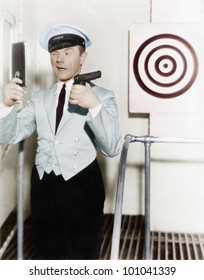 Young man looking at a mirror and aiming at a dartboard with a handgun