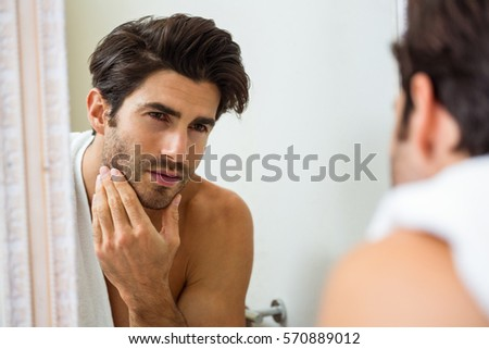 Young man looking in mirror and checking his stubble in bathroom