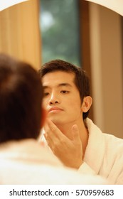 Young man looking in mirror, touching his face