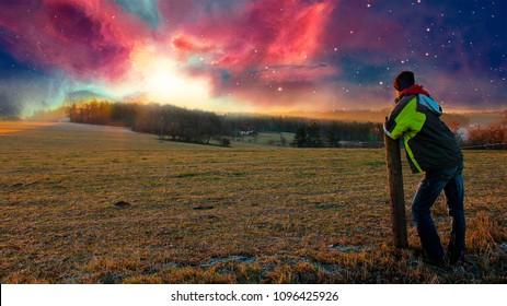 Young man looking to nebula sunset, photo manipulation