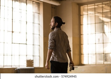 Young man is looking for the new shot in the old industrial space with big factory windows. Photographer is standing in the factory and ready to take photographs. Color toned image.