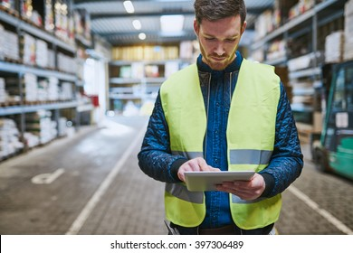 Young man looking up order details on a tablet as he shops in a hardware warehouse for supplies , close up upper body