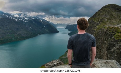 Young man looking out over Gjende Lake during besseggen ridge hike in Jotunheimen National park, Norway.