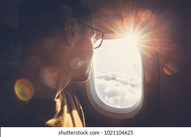 Young man looking out through window of the airplane during beautiful sunrise.