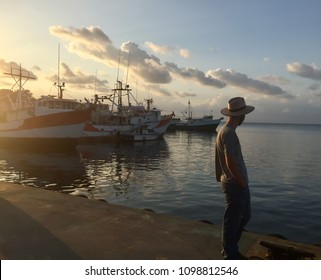 Young man looking out towards ships docked in the ocean set against a deep yellow sunset in Guanaja, Bay Islands, Honduras