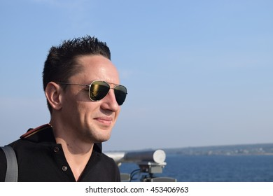 Young man looking at the sea through sunglasses