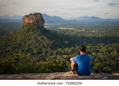 Young man looking at the Sigiriya Rock from Pidurangala rock in Sri Lanka