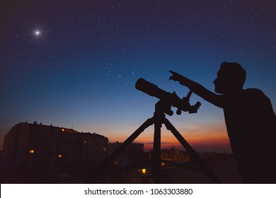 Young man looking at the sky with astronomical telescope in urban surroundings. My astronomy work.