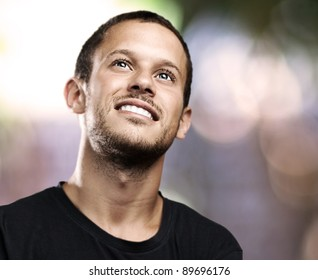 young man looking up and smiling at house