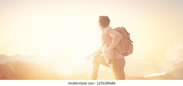 Young man is looking at sunset. Traveller with backpack.