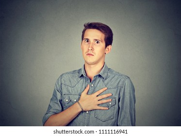 Young man looking super dumbfounded with unbelievable news holding hand on chest and looking stunned at camera