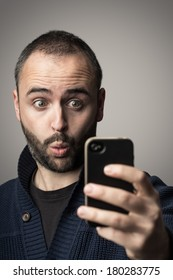 Young man is looking surprised at his phone.