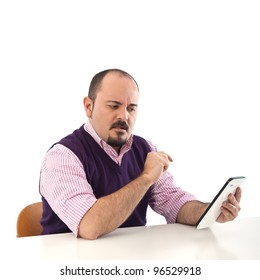 Young man looking at tablet with confused expression.