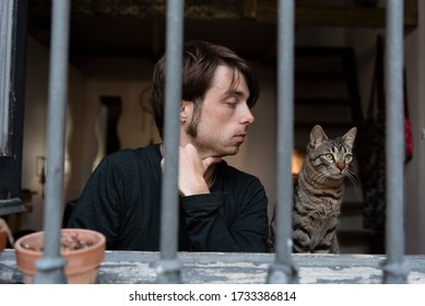 Young man looking through a barred window with his cat