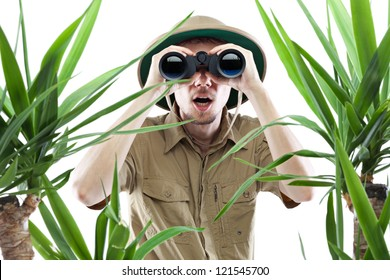 Young man looking through binoculars with an amazed expression, palm trees on foreground out of focus, isolated on white