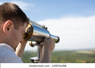 Young man looking through binoculars to the landscape panorama in sunny day. Space for text