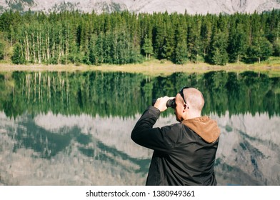 Young man looking through binoculars in National Park