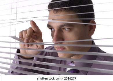 Young man looking through the blind. White background in studio.