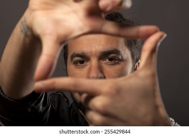 young man looking through fingers frame