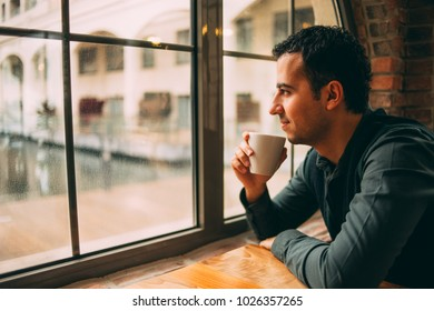 Young Man Looking Through a Window in a Rainy Day