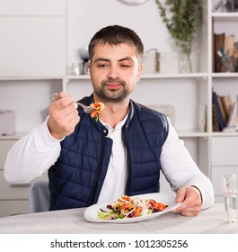 Young man looking at vegetable salad and eating at table indoors