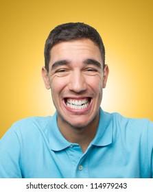 Young man looking very happy over light orange gradient