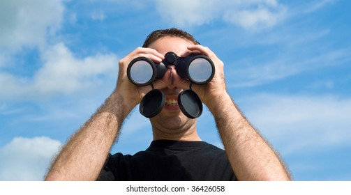 A young man looking at the viewer with a set of binoculars, with a blue sky behind him