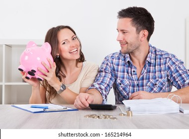 Young Man Looking At Woman Inserting Coin In Piggybank