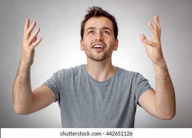 Young man looking up and worship God with raised hands