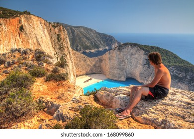 Young man looks down on Shipwreck beach on top of the high cliffs on the island of Zakynthos in the afternoon