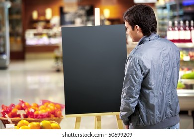 The young man looks at an empty board in shop
