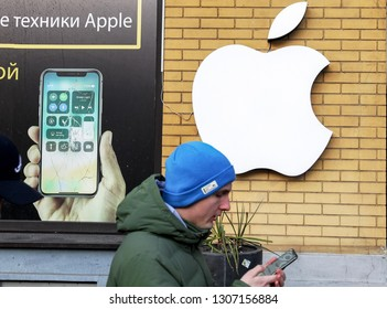 an young man looks on smartphone walking next to Apple brand logo on yellow wall of a repair service of mobile devices in Kiev,Ukraine, 07 February 2019.
