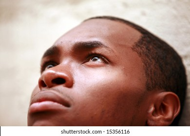a young man looks up to the sky while deep in thought