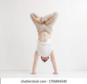 Young man with lotus pose doing handstand balance exercise. Yoga and gymnastics workout.