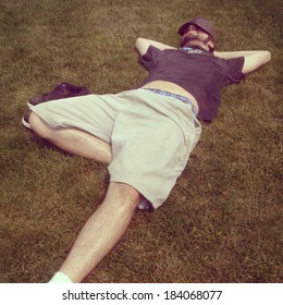 Young man lounging in grass, instagram style