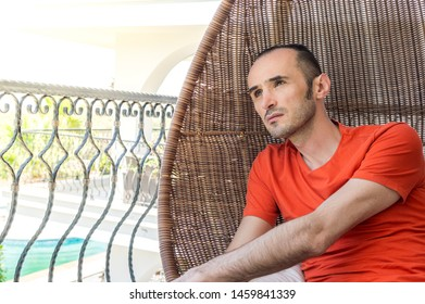 Young man lounging, looking in distance, dreaming about good future on swinging chair in balcony on a hot sunny day. Travel and relaxing concept.