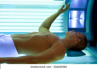 young man lying in bed  solarium adjusts tanning booth