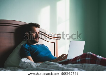 Young man lying in the bed working on a laptop