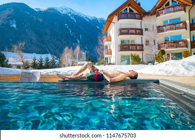 Young man lying by the open pool in the middle of the mountains in Alps. SPA by the outside warm pool at the ski resort.