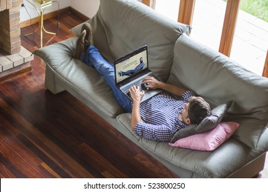 Young man lying comfortably on the sofa while using laptop with video streaming website on the screen. View from top. All screen graphics are made up.