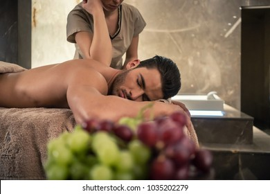 Young man lying down during traditional acupressure procedure of Thai massage at luxury spa and wellness center