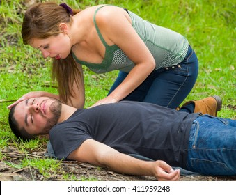 Young man lying down with medical emergency, young woman sitting by his side performing light treatment, outdoors environment