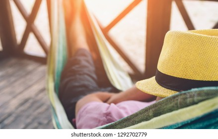 Young man lying in hammock at sunny beach by ocean and sleeping. He hold had on face. Young man chilling.