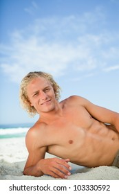 Young man lying on the beach while looking at the camera and showing a great smile
