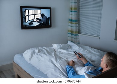 Young Man Lying On Bed Watching Television In His Living Room