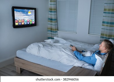 Young Man Lying On Bed Watching Television In His Bedroom